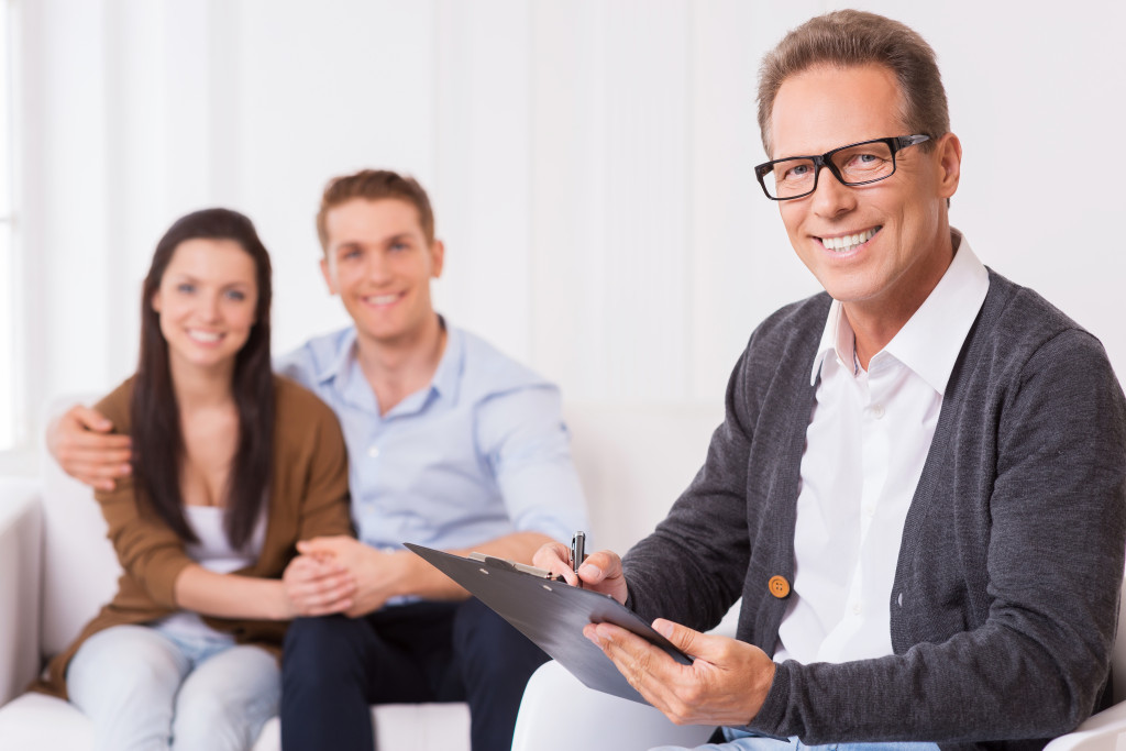 Confident family psychologist. Confident psychiatrist writing something in clipboard and smiling while cheerful couple sitting in the background and holding hands